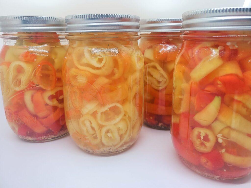 pickled banana pepper rings in four mason jars