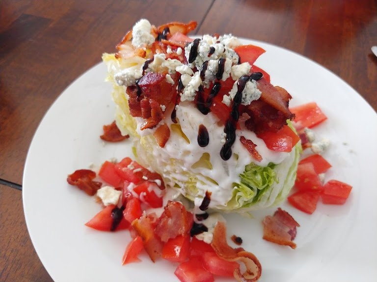 classic wedge salad on white plate.