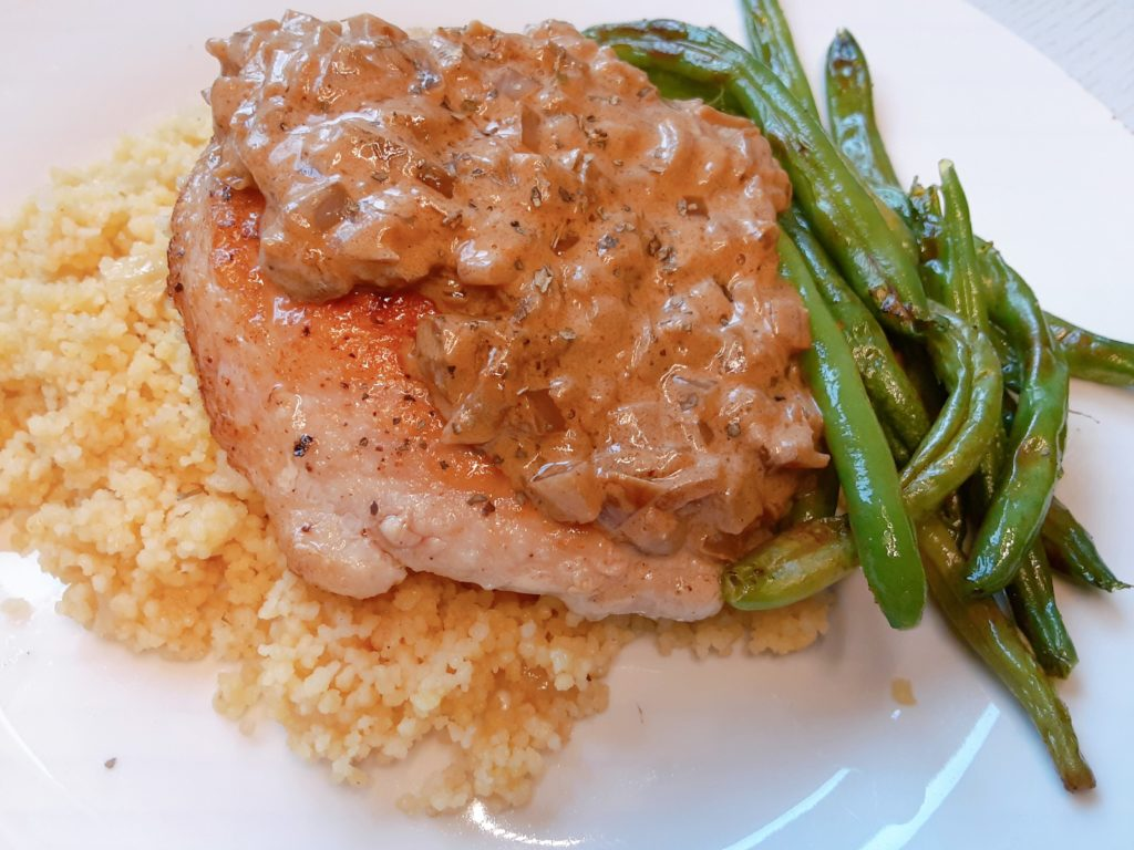 A deliciously tender and lean pork chop with a creamy, onion sauce served with couscous and green beans for a restaurant quality meal you can make at home for under $10!