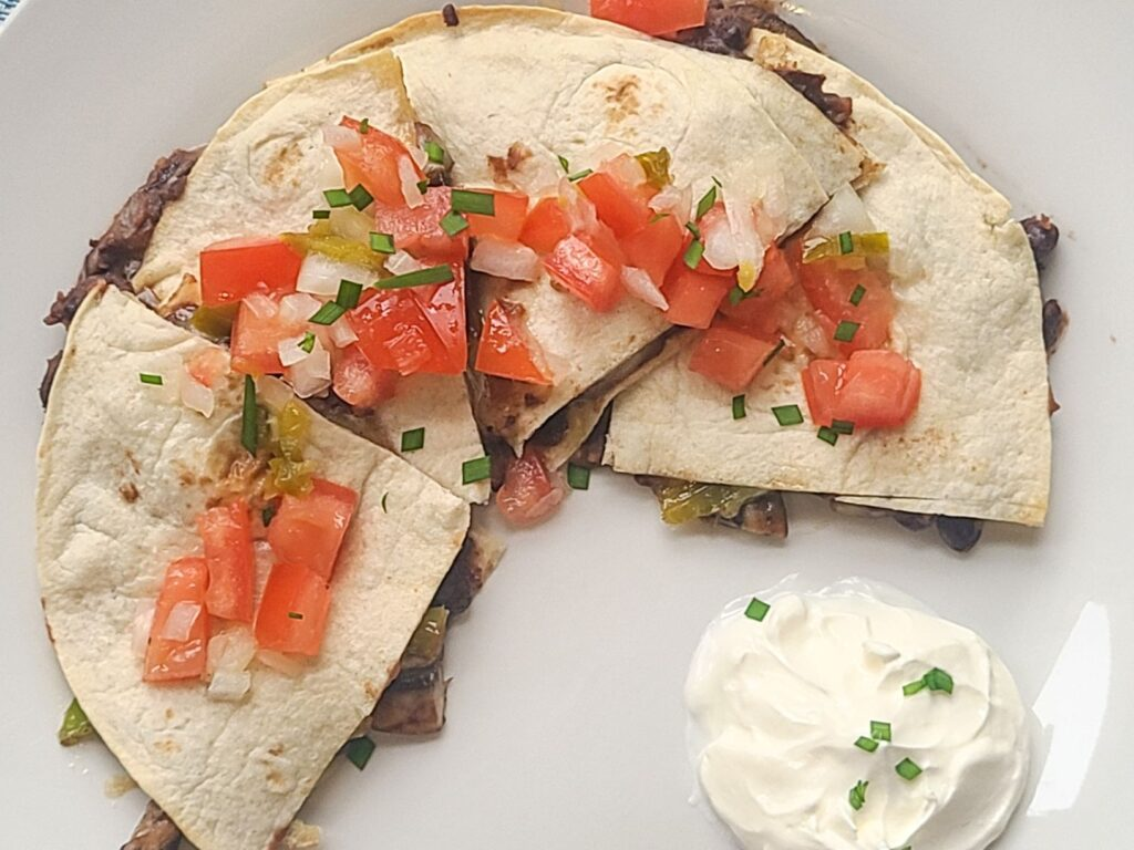 Black bean quesadilla topped with tomato salsa cruda on a white plate and a dollop of sour cream