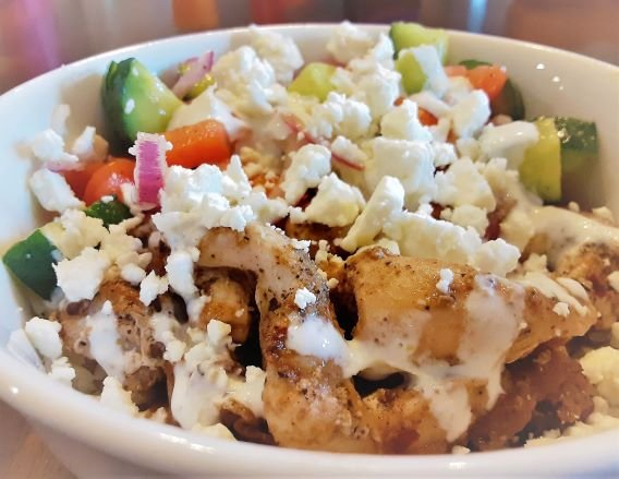 chicken and rice bowl with feta cheese cucumbers tomatoes and onions