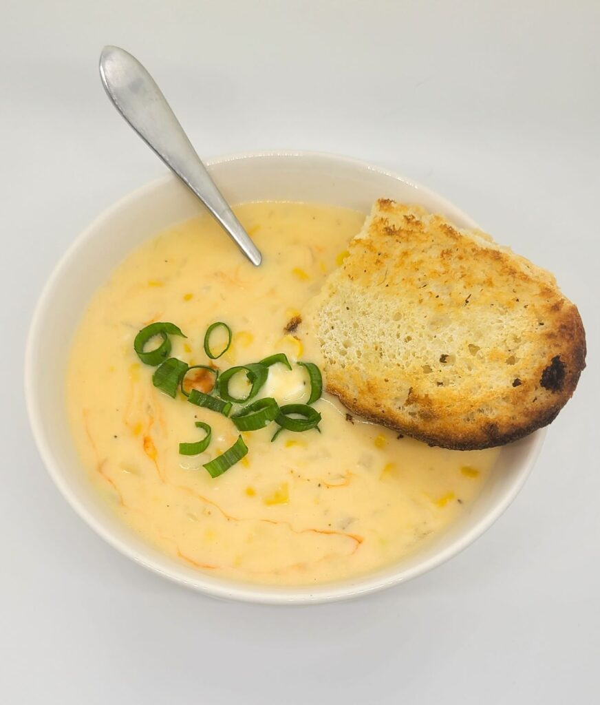 Corn soup recipe topped with scallions, drizzled with hot sauce and served with garlic toast in a while bowl