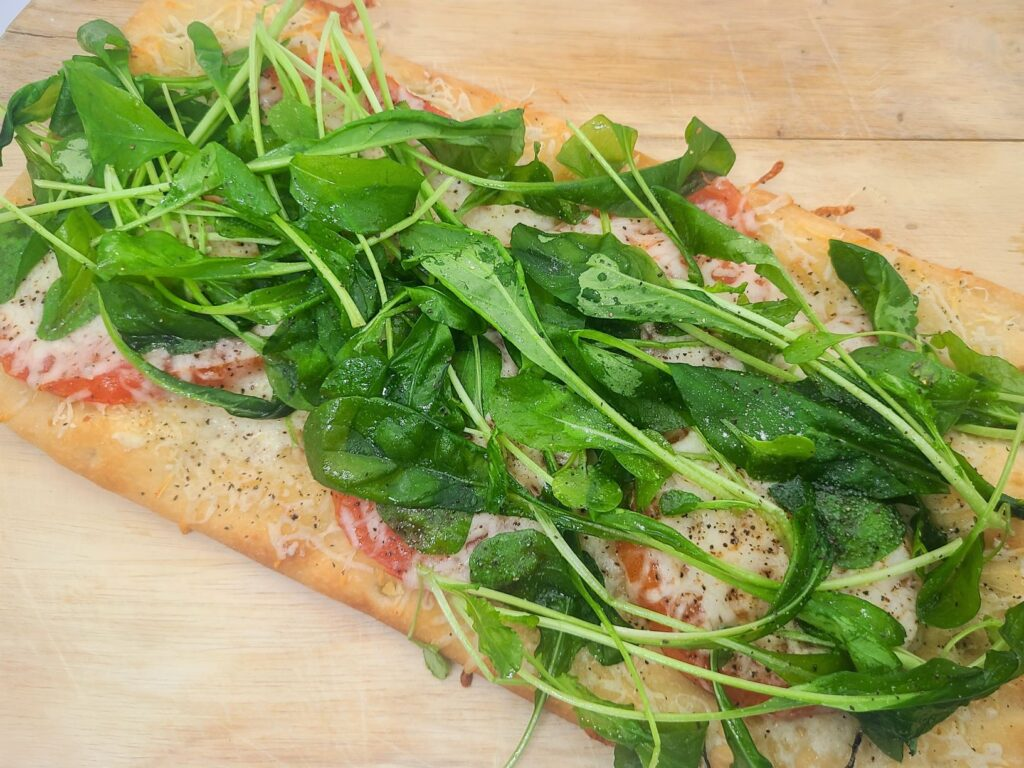 fresh ingredients with arugula and tomatoes on top of flatbreads